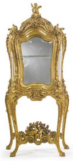 A FINE AND ELABORATELY CARVED ROCOCO STYLE GILTWOOD VITRINE FRANCE, LATE 19TH CENTURY, MOST PROBABLY AFTER A DESIGN BY LÉON MESSAGÉ all glass sides of bombé form, the single door opening to a mirrored interior fitted with one glass shelf height 7 ft. 1 in.; widt 37 1/2 in.; depth 20 in. 216 cm; 95 cm; 51 cm
