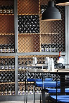 Large caged cupboards used for storage in this cafe giving the space an industrial style. The look is further achieved with the repetition of bottles creating clean lines and a sense of order.: