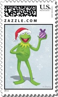 Kermit the Frog in a Santa hat and holding a purple present. Soft snowy background on this Disney Christmas stamp.