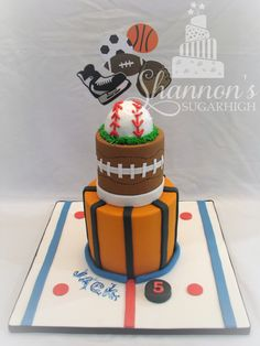 Tiered, fondant covered sports themed cake for a boy turning 5! Cake board is decorated as a hockey rink, 1st tier is a basketball, 2nd tier is a football. Includes a mini cake shaped as a baseball on top and cardstock toppers. Bottom tier: vanilla cake, vanilla buttercream, chocolate ganache frosting; top tier: chocolate cake, vanilla buttercream, chocolate ganache frosting.