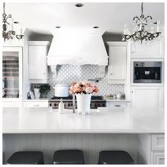 All white kitchen with misty carrera Caeserstone countertops and vintage chandeliers - Jillian Harris home