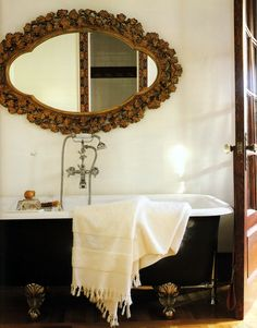 Stunning frame for oval mirror over black painted claw footed tub with wall mounted faucet.