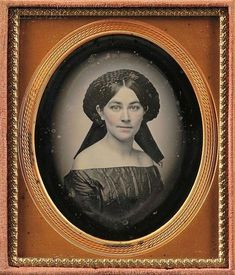 An halo of braided hair! Bare shoulders must have seemed very erotic in the 1840s and 50s. This young woman's face and shoulders are lovely. She wears no jewelry and her eyes are so alert.