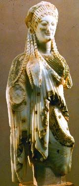 """ARCHAIC SCULPTURE: Kore, from Chios c. 520 B.C. Marble, height 21 7/8"""" Ornate refined grace. Garments loop around body in soft diagonal curves. Play of richly differentiated folds, pleats and textures. Linear pattern. Stylized and beaded hair. Lively natural smile. Found in Acropolis of Athens. LOCATION: ACROPOLIS MUSEUM, ATHENS"""