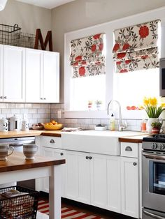 Love this kitchen!  Wire baskets, pop of color in curtains, butcher block countertops, farmhouse sink, island, chef's stove, and big windows!