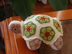Tartaruga de crochê feita com motivos African Flower, linha 100% algodão nas cores vermelho telha, verde claro, verde escuro, manteiga, caramelo, bege e preto.  Enchimento com fibra sintética antialérgica.  Comprimento (cabeça ao rabo): 22 cm  Largura: 16,5 cm  Altura: 10 cm
