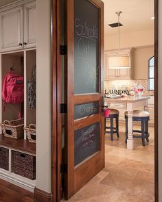 A chalkboard 3 panel door opens to a traditional mudroom boasting wicker bins sitting under a wood bench top accenting French white mudroom open lockers located below cabinets fitted with bronze knobs.