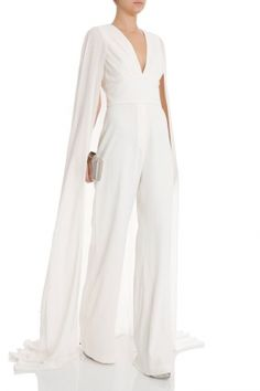 Elie Saab Bklss Jumpsuit W Train - Deep v neckline and banded waistband - Cut out back with sheer cape design - Concealed side zip fastening Styled with: Alaia shoes, Kotur clutch Jumpsuit With Train, Prom Jumpsuit, Wedding Jumpsuit, Cape Jumpsuit, White Pantsuit, White Jumpsuit, White Romper, Wedding Pantsuit, Wedding Suits