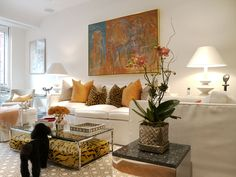 A painting by George Negroponte hangs above a white outdoor-fabric covered couch. Tiger patterned floor pillows tucked beneath a glass and steel coffee table provide extra seating when needed. The mirrored side table was designed by Cathy's father, Theodore D. Triant.