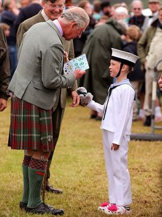 A boy presents Prince Charles with a card and teddy bear for his grandson Prince George