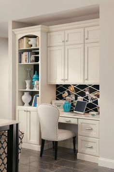A built-in desk in kitchen with bookcase and cabinets.
