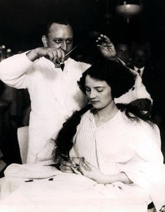 """Hotel McAlpin, barber shop, 1920s - a woman trades her long locks for a fashionable bobbed cut. Women went to barbers as they could cut hair better than beauticians, it wasn't until after the """"Bob Haircut"""" that beauty shops or salon started to learn to cut styles! Before they gave perms, curled, henna color, or styled hair only."""