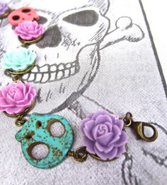 Day of the Dead Bracelet, sugar skull and sugar flower original Bella design, pastel purples, pinks, and turquoise. $20.00, via Etsy.