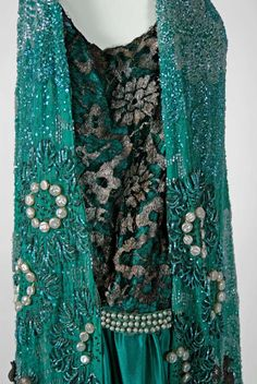 1920's French Teal-Blue Beaded Silk Chiffon & Metallic Lace Dress The garment's simple unstructured style allows freedom of movement and the beadwork and appliqués are fine examples needle art. The beading is made up of five different mediums and embellished with a floral pattern.The garment slips over the head with no closures. Detail 4 Private Collection