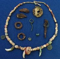 Anglo-Saxon woman (grave no. 27) at Wheatley in Oxfordshire. In total 61 amber beads, 2 blue glass beads, a cube shaped bead, a flattish bead with a wavy white strip, several cylindrical beads of pale transparent glass made to look like several smaller beads together and a bead made from a piece of bone or ivory. Also several objects used as pendants: two small perforated Roman coins, from the Emperor Constantius II (AD337-360), two wolves or dogs canine teeth and a small boars tusk.