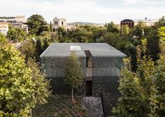 A chequerboard screen of glazed ceramic tiles in various green hues wraps this house in Barcelona, helping it blend in with the surrounding gardens.