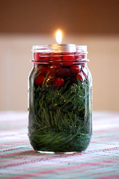 ~mason jar, greenery, cranberries, water, tea light~    simple Christmas table centerpiece    done! :-)    Idea from Better Homes and Gardens.    Definitely going to make some of these next year.