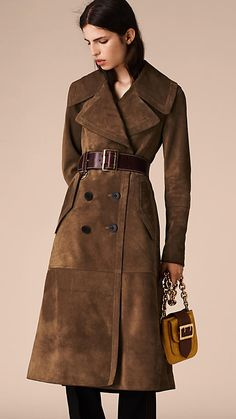 A suede coat cut with a classic double-breasted closure and wide revere collar. The tapered waist features an integrated martingale to cinch the silhouette and a softly pleated skirt for movement.