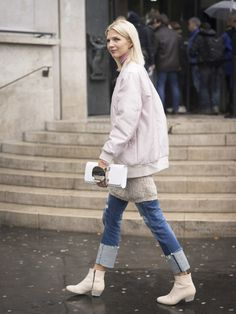 A pink bomber jacket paired with jeans and ankle boots.