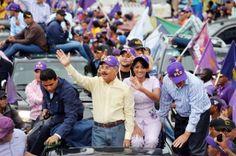 El presidente-cadidato presidencial a la reelección, Danilo Medina, acompañado de su esposa Cándida Montilla y del jefe del Cuerpo de Ayudantes Militares, mayor general Adán Cáceres, del Ejercito Nacional (en traje civil oscuro), encabeza la caravana de cierre de campaña del PLD y aliados, en el Malecón de la capital.