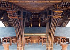 Trumpet-shaped columns made from bamboo cane support the thatched roofs of this restaurant and bar designed by Vo Trong Nghia for a spa resort in Da Nang