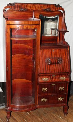 VICTORIAN SLANT FRONT DESK/SECRETARY/BOOKCASE, SINGLE DOOR WITH CURVED GLASS WHICH REVEALS FOUR WOOD SHELVES, SLANT FRONT DESK HAS SEVEN PIGEON COMPARTMENTS AND A SINGLE DRAWER THAT IS ABOVE THREE DRAWERS, ABOVE THE DESK IS A BEVELED MIRROR