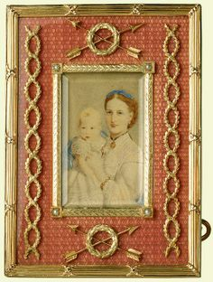 Fabergé rectangular frame of silver-gilt with salmon pink guilloché enamel, chased twice with crossed arrows and foliate wreaths, twice with foliate caducii; edge with reeded and tied mounts. Foliate bezel with half-pearls at corners, inset with photograph of Queen Alexandra, when Princess of Wales, with her son Prince Albert Victor. Mark of Michael Perchin.