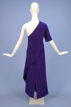 MADAME GRES ASYMMETRICAL THREE PIECE SILK ENSEMBLE, 1970's. Fitted royal purple silk crepe one-shoulder tunic with right elbow length sleeve and long angular panel on left side, worn over either wide leg trousers or narrow full length skirt, both with back zipper. Back