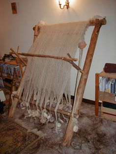 Reproduction of a primitive warp weighted loom, set up for tabby pile weave, with tablet woven edges