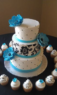Black and teal floral wedding cake with cupcakes.