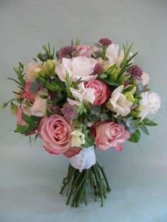This romantic bouquet contains antique pink and cream roses, cream freesia, sweet peas and astrantia with a mixture of herbs.
