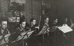 Anonymous | Orkest van de Luftwaffe, Anonymous, 1941 - 1942 | Luftwaffe militairen spelen muziek, op blaas- en snaarinstrumenten. Voor hen een standaard met muziek. Aan de muur een plaat van een ploegende boer en een filmaffiche.