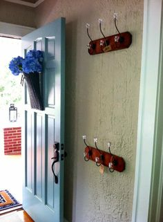 Two rows of hooks for visitors to place belongings in a small entry way.
