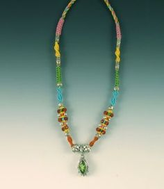 This Isha Elafi Joy necklace is so cute and fun! It has a green pendant and is set around a green, blue, and yellow color scheme!