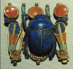 an elaborate Scarab Beetle made of lapis lazuli, used as a piece of jewellery for king Tutankhamun. It has a sun disc above it and is flanked by two cobras also wearing a sun disc. This jewel is actually a version of the King's name in hieroglyphs.