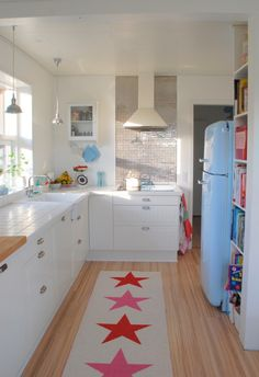 Kitchen love, love the wall of shelves for cook books and the blue refrigerator, maybe a Smeg? Cute runner.