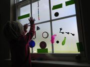 put contact paper on the window and let them stick all kinds of objects on it
