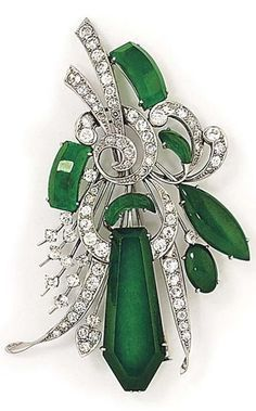 AN ART DECO PLATINUM JADEITE JADE AND DIAMOND BROOCH. Designed as a stylised floral spray with claw-set vari-shaped jade panels and circular-cut diamond openwork detail circa 1930. #ArtDeco #brooch