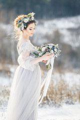 Beautiful bride admiring wedding bouquet. Winter wedding. Winter wedding bouquet.