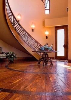 A round foyer with a sunburst wood floor is accentuated with a custom-built curved staircase with iron railing  (via Handmade Curved Stair Railing by Brian Hughes Artist Blacksmith   CustomMade.com)