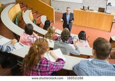 Elegant teacher with students sitting at the college lecture hall