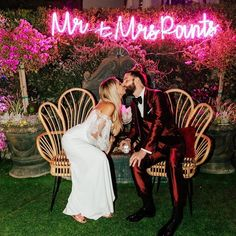 Couple in front of a neon pink last name sign, fun wedding sign ideas {Alexandria Monette}
