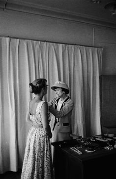 Coco Chanel adjusting jewels on an assistant in her Paris atelier captured by Mark Shaw for LIFE Magazine in 1957
