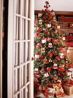 Новогодняя елка украшенная коробочками и красными елочными шариками.