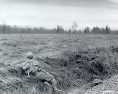 During the Battle of the Bulge, US soldiers of Co. M, 3rd Battalion, 18th Infantry Regiment, 1st Infantry Division, keep low along the edge of the forest near Sourbrodt, 18 december 1944.