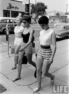 Three women in contemporary summer casual fashions walk along North Rodeo Drive in Beverly Hills in the 1950s. The Amelia Gray store is visible across the street at the northeast corner of Brighton and Rodeo, and a Joseph shop is under contruction at the  southeast corner of the intersection.