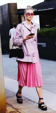 Ruby Jean Wilson in a pink Tome jacket and a pleated matching skirt with strappy black platform heels