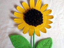 sunflower made from a paper plate with brown pom poms in the middle