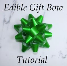 Learn how to make this shiny totally edible gift bow! Bow is made from a gelatin based recipe which gives it the glossy shine! Tutorial would work well for wafer paper bows too! Great for present cakes, Christmas cakes, birthday gift box cakes!