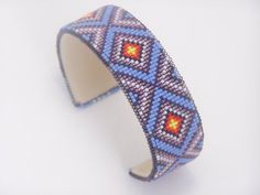 This American Indian beaded bracelet with the classic Diamond Back pattern is made with the blends of Purples and Lavender along with a splash of fire colors of the Southwest . The base used for this